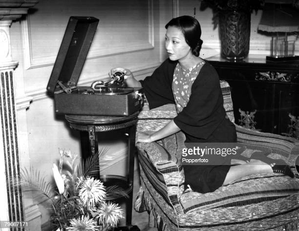 November 1934 American actress Anna May Wong pictured at her home playing a record on her gramophone player