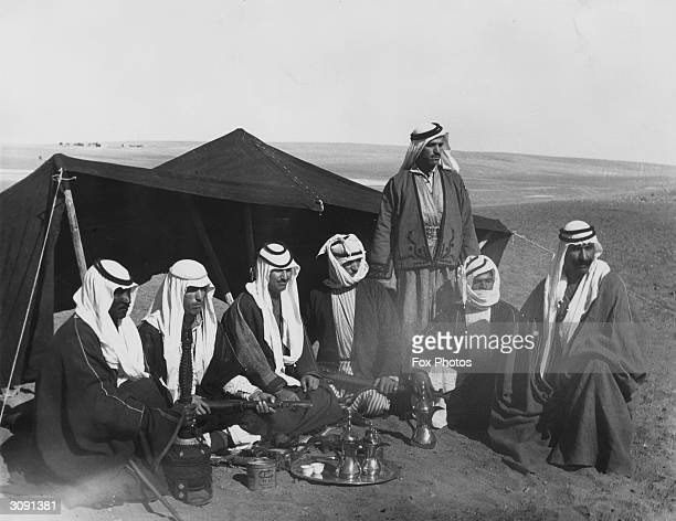 A group of Bedouin men in traditional headdresses seated around coffee pots in front of a tent