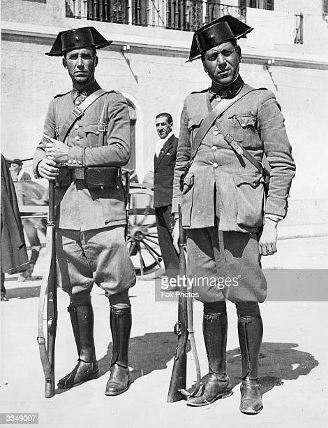 Two Spanish civil guards standing in the street with their weapons