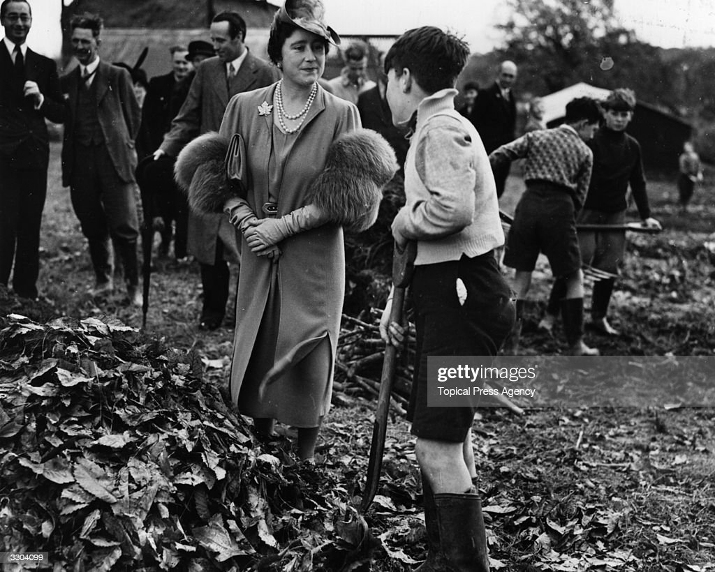 Queen Elizabeth (1900 - 2002), Consort to King George VI talking to a young evacuee whilst he works in the garden of an evacuation school at Horsted Keynes in Sussex.