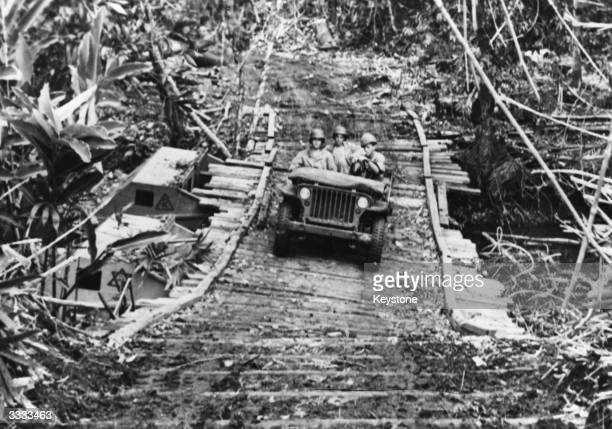 Soldiers in a Jeep crossing a makeshift bridge in the jungle on Guadalcanal with amphibian tractors as its base.