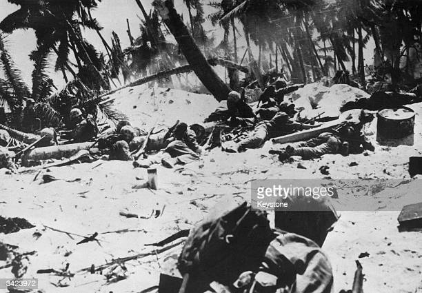 American Marines crouch down amidst Japanese fire on Tarawa Gilbert Islands while the leader points to Japanese entrenchments Over 1000 Marines were...