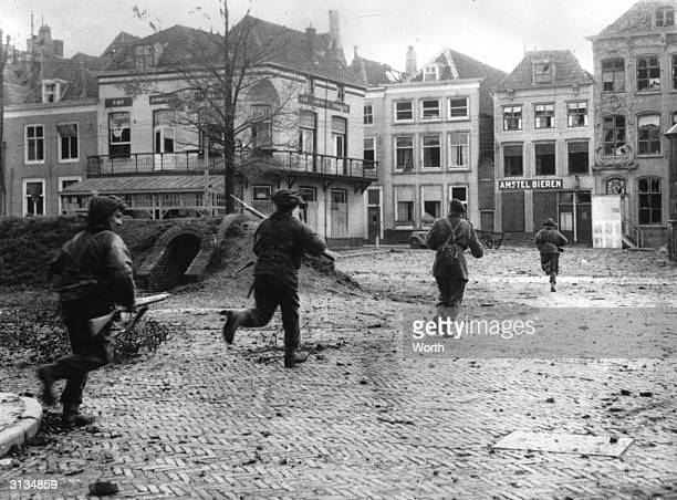 Allied assault troops dash through the streets of Flushing in the Netherlands to clear out the remaining enemy snipers after the World War II...