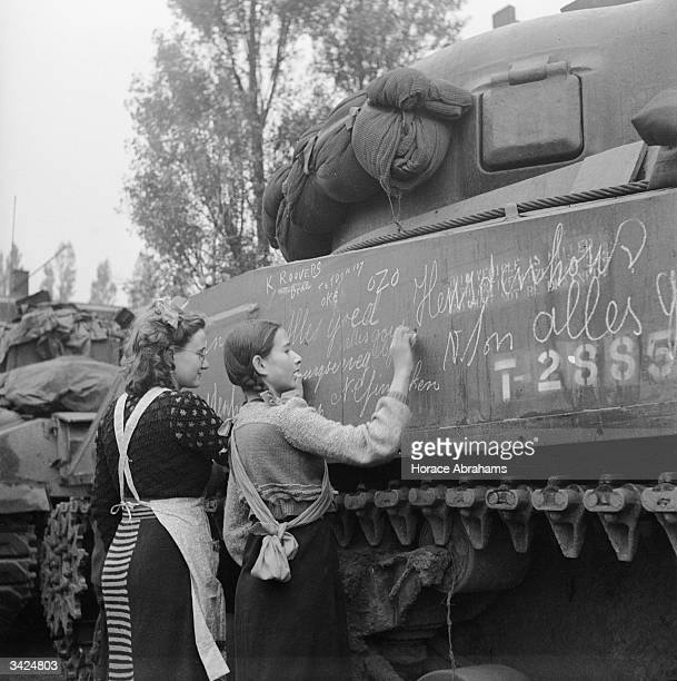 Two Dutch girls write slogans of welcome on tanks after the liberation of Breda by Polish troops.