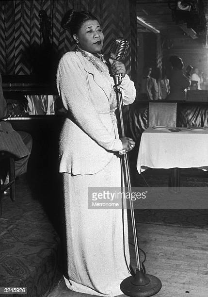 EXCLUSIVE Fulllength view of American jazz singer Ella Fitzgerald dressed in a white beaded gown gripping a microphone stand onstage at a night club