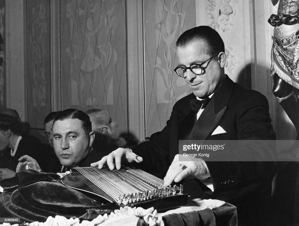 A guest temporarily suspends his drink to watch Anton Karas (1906 - 1985) play the music he wrote for the film 'The Third Man' on his zither. Karas is sitting on his specially draped dais at the Empress Club in London.