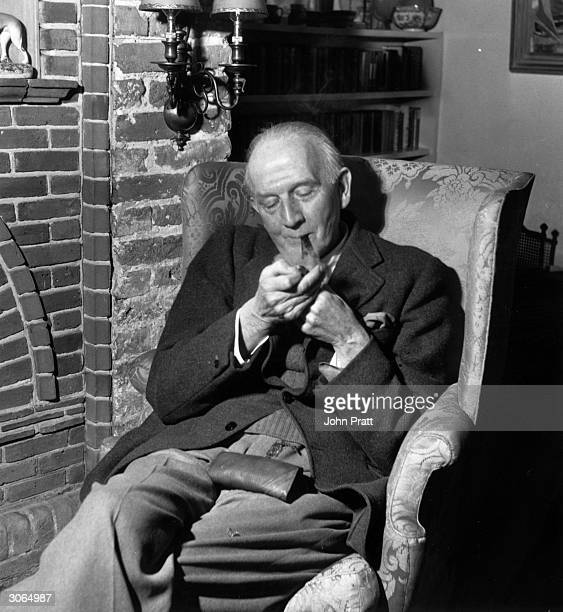 English author A A Milne lighting his pipe at home at Hartfield Sussex