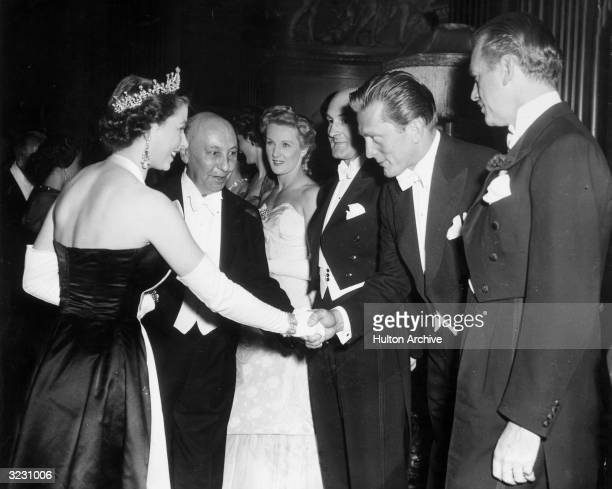 American actor Kirk Douglas bows and shakes hands with Queen Elizabeth II as American actor Douglas Fairbanks Jr looks on at the Royal Command...