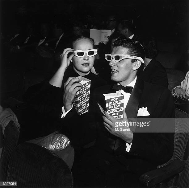 EXCLUSIVE American actor Keefe Brasselle and his wife Norma wearing 3D glasses and holding boxes of hot buttered popcorn sit in the theater at the...