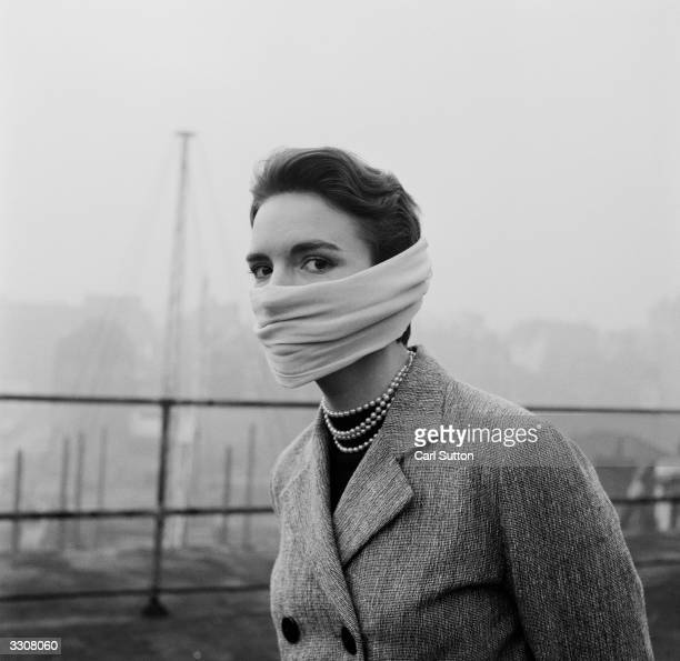 Julie Harrison of the Hulton Press tries out a protective mask to combat the effects of London's smog. Original Publication: Picture Post - 6799 -...