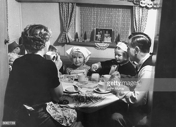 A family enjoy a meal in their caravan home at Cranbourne Hall Windsor Berkshire where a selfcontained community has been set up on the site with...