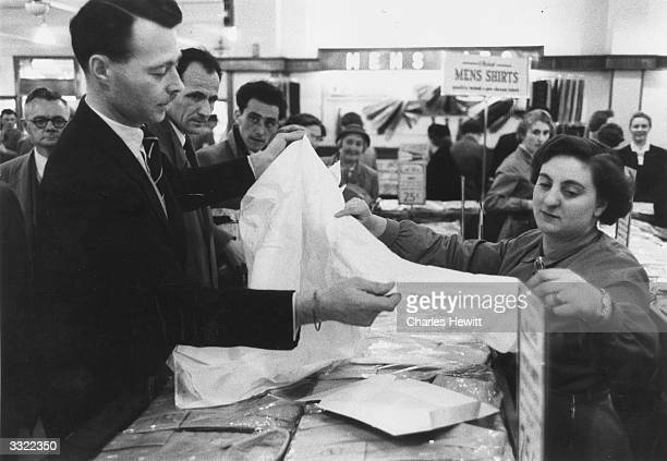 A salesgirl helping a customer to choose a shirt in a busy Marks Spencer's store Original Publication Picture Post 8437 Scientific Shopping unpub