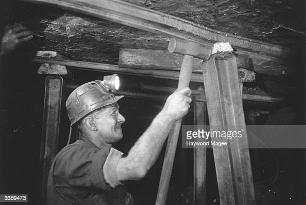Miner in the Cwm Gorse colliery, Pontypridd, Wales wedging in a pit prop. Original Publication: Picture Post - 8444 - Coal Production - unpub.
