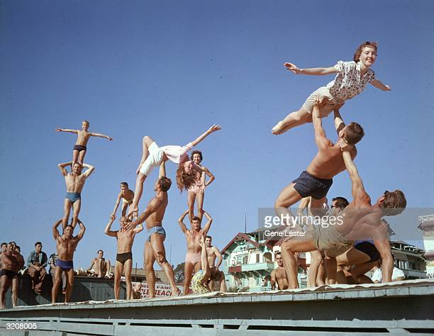 EXCLUSIVE A group of men women and children in swimsuits posing in gymnastic formations at Muscle Beach Santa Monica California
