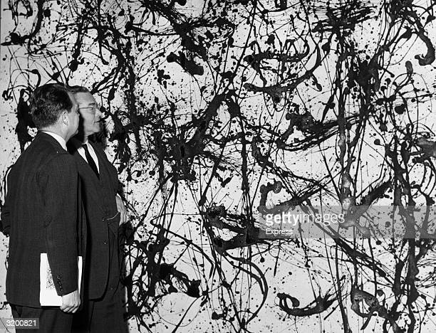 John Hay 'Jock' Whitney the US ambassador to Great Britain and Porter McCray of the Museum of Modern Art looking at a Jackson Pollock painting at an...