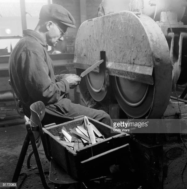 Worker cleaning new carving knife blades during the abrasive process that follows knife grinding at a Sheffield steel factory.