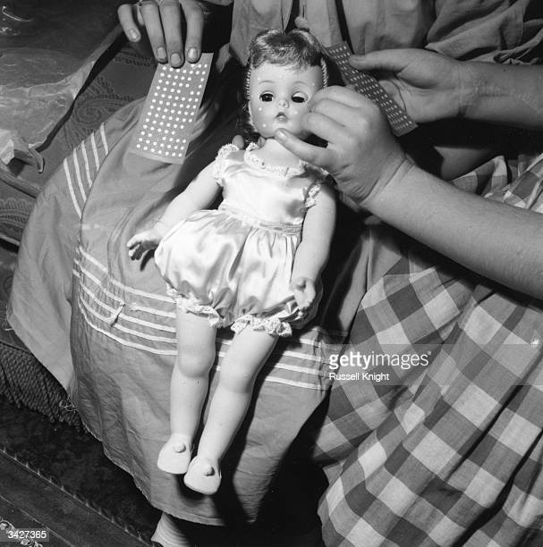 An American-made child's doll which has stick-on chicken pox and injuries as accessories.