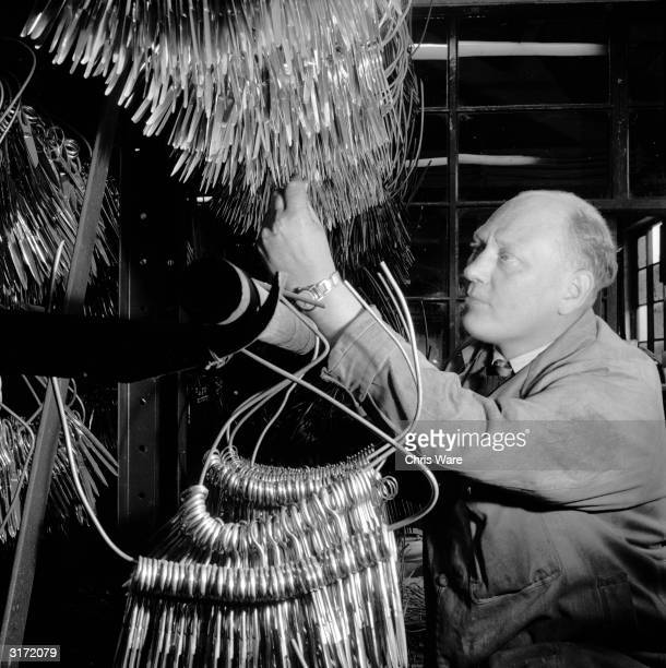 Partly finished scissors being inspected by the scissor department foreman, H Woke, who has worked at the Sheffield steel firm for 29 years.