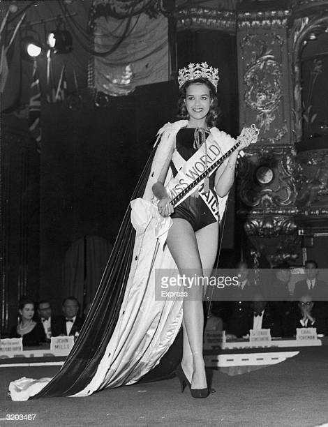 Fulllength image of the winner of the Miss World beauty pageant Miss Jamaica Carole Joan Crawford walking across a stage in a swimsuit a crown and a...