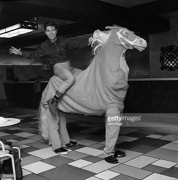 English pop star Cliff Richard riding a pantomime horse during rehearsals for the Christmas show 'Aladdin and his Wonderful Lamp' at the London...