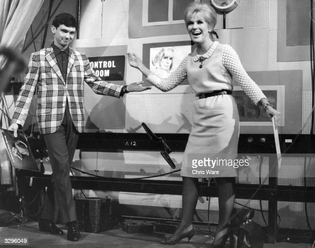 Pop singers Gene Pitney and Dusty Springfield , holding copies of each others records, share a joke on the set of British television music show...