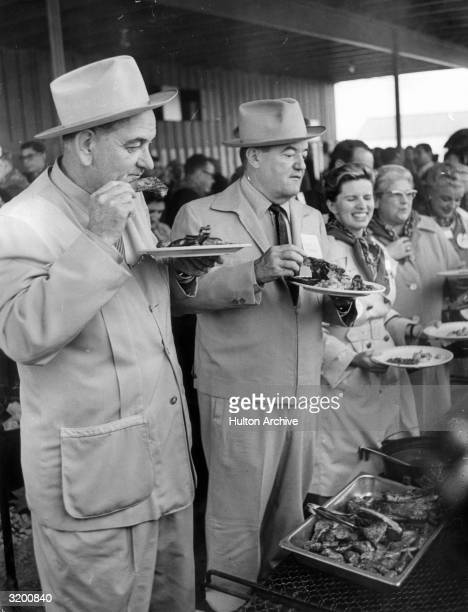 US president Lyndon B Johnson and Vice Presidentelect Hubert Humphrey eat ribs at a victory barbecue after they won the presidential election Austin...