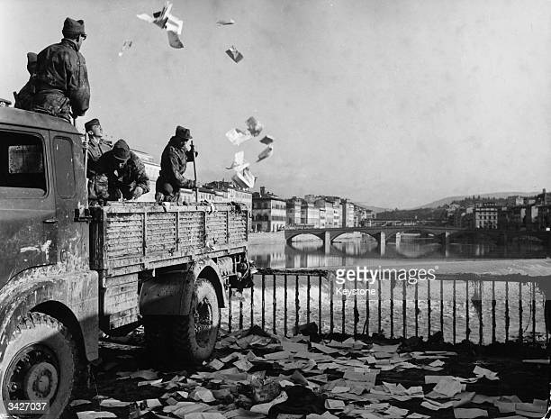 Italian soldiers clearing away debris from the streets of Florence after devasting floods when the Arno broke its banks The debris is being thrown...