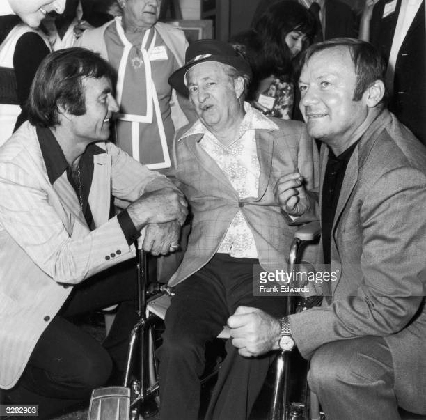 American actor and comedian Larry Fine of the comedy team the Three Stooges sits in a wheelchair next to American actor director and producer George...