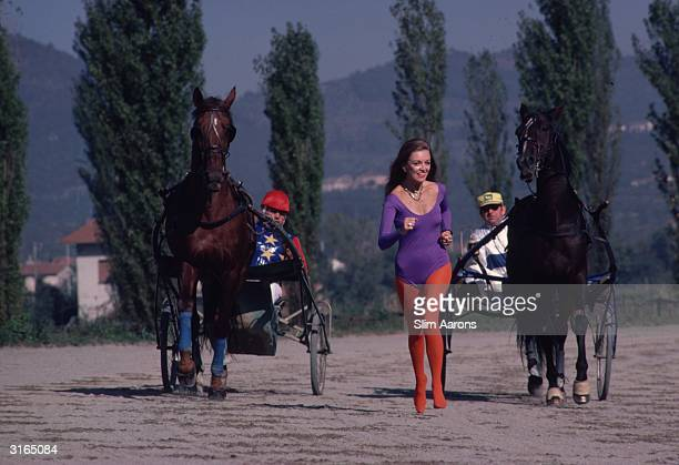 MarieLouise Scio in leotard and tights running between two racing sulkies in the health resort of Montecatini Italy She is the American wife of Baron...