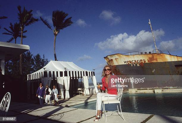 Molly Wilmot by a swimming pool in Palm Beach Florida with the hull of a rust clad ship looming in the background