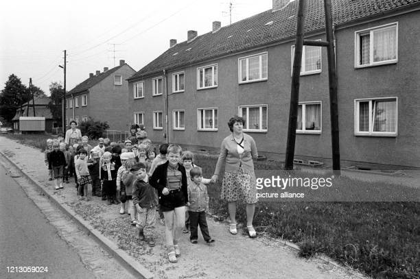 November 1986, Saxony, Trossin: At the end of the 1980s, a kindergarten group passes two-storey apartment buildings in the village of Trossin . Exact...