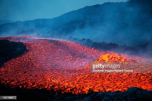 November 2006 - Boulder rolling in lava flow at dusk during eruption of Mount Etna volcano, Sicily, Italy.