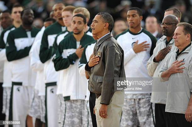 President Barack Obama stands with Michigan State during the singing of the National Anthem during the Quicken Loans Carrier Classic NCAA basketball...