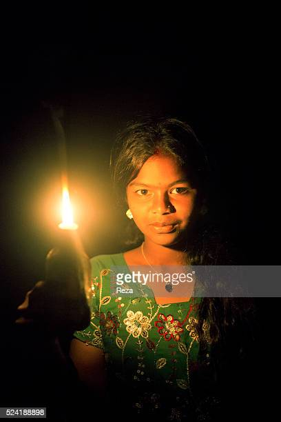 November 2013 Coffee Plantation Chickmagalur India Candle that lights the face of the young daughter of farmers in a coffee plantation The candle...