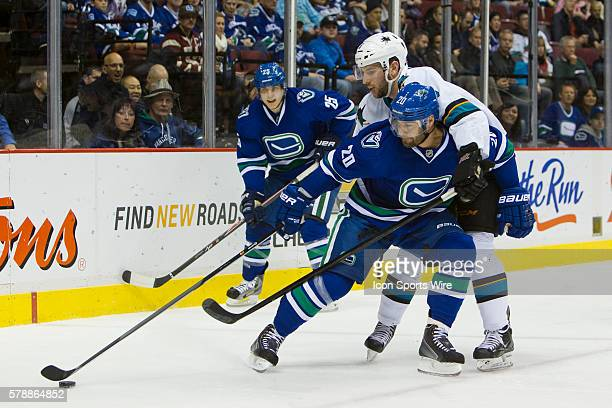 Third Period - Chris Higgins of the Canucks and Jason Demers of the Sharks battle for the puck as Mike Santorelli of the Canucks looks on during a...