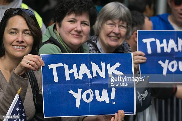 11 November 2014 Crowds hold a sign of thanks at Veterans Day celebrations in the Manhattan Borough of New York New York USA