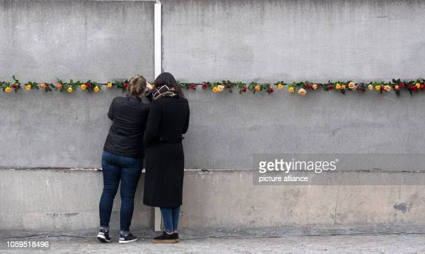 November 2018, Berlin: Participants of a commemoration ceremony for the 29th anniversary of the fall of the Berlin Wall are stuck at the wall...