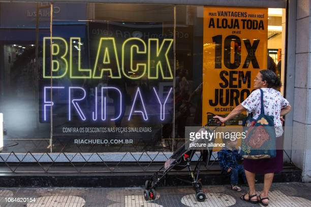 A woman and a child take a break in front of a shop window Black Friday in Sao Paulo has attracted many people to the shops Photo Warley Kenji/dpa