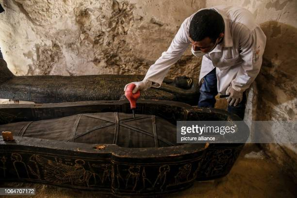 An archaeologist inspects a sarcophagus inside a tomb at the alAssassif Necropolis The tomb of the overseer of the mummification shrine has been...