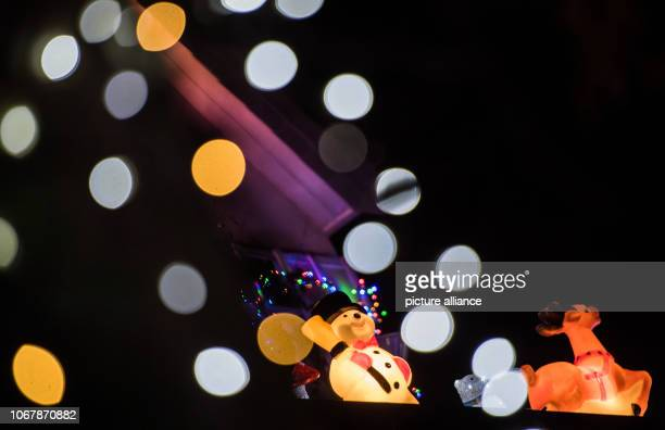An illuminated snowman and a reindeer stand between the colourful chains of lights Christmas woman Christine as the 62yearold calls herself has been...