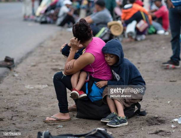 A migrant waits with her children on the edge of a country road in the Mexican city of Isla Currently thousands of people from Central America in...