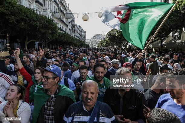 Algerians take part in an antigovernment demonstration demanding the ouster of officials who served under expresident Abdelaziz Bouteflika as they...