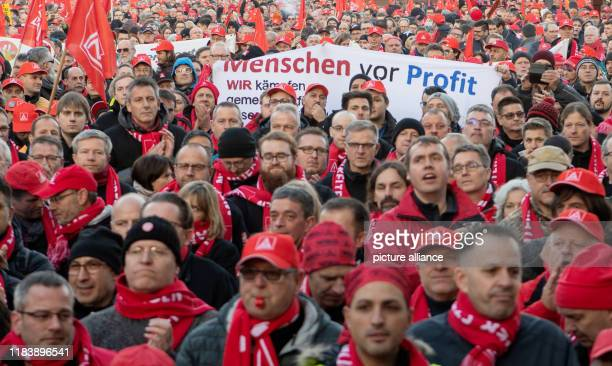 """November 2019, Baden-Wuerttemberg, Stuttgart: Participants of a nationwide IG Metall action day hold a banner with the inscription """"People before..."""