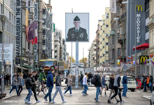 November 2019, Berlin: Passers-by walk past Checkpoint Charlie, the former border crossing between West and East Berlin. The showmen disguised as...