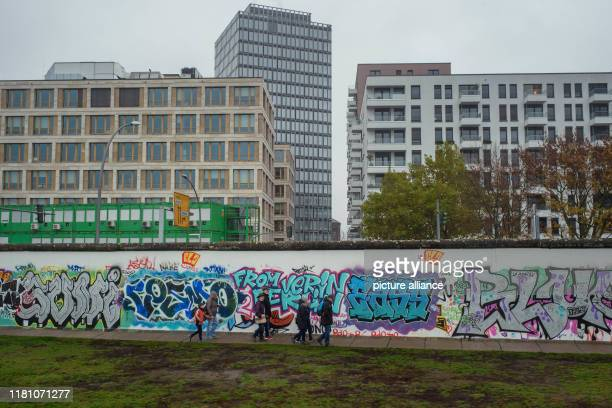 November 2019, Berlin: Tourists walk along the west side of the East Side Gallery, the former Berlin Wall. In the background, residential and office...