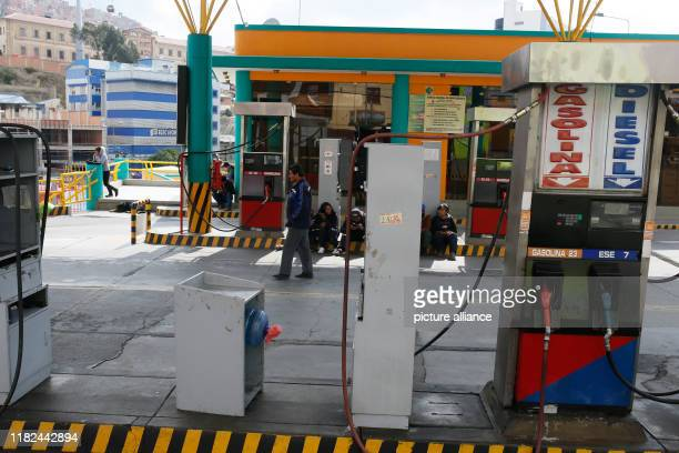 Employees sit at a gas station in La Paz Petrol stations run out of fuel because former President Morales's followers blocked the main road Photo...