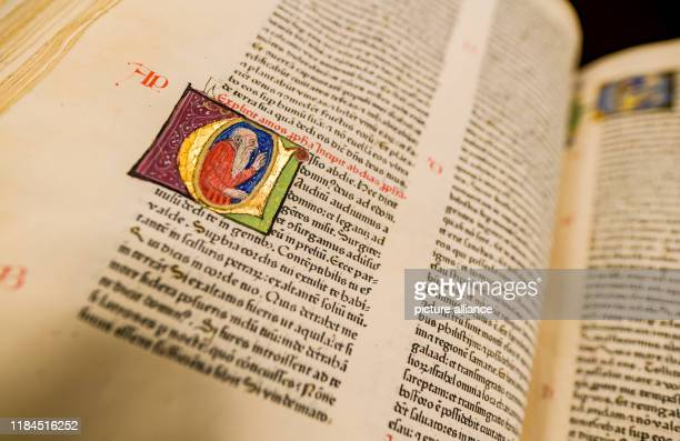 A volume of a Bible from Gutenberg's printing press which is auctioned off in an anniversary auction of valuable books stands on red velvet at...