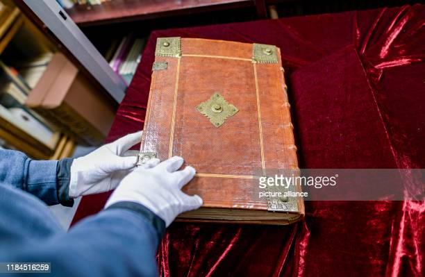 An employee of Ketterer Kunst a Hamburg art auction house leafs through a volume of a Bible from Gutenberg's printing press which is auctioned off in...