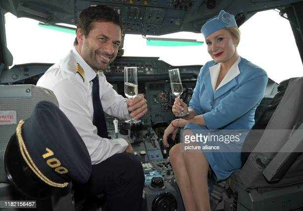November 2019, North Rhine-Westphalia, Cologne: The actors Kai Schumann and Janine Kunze sit in the cockpit of an airplane while filming the 100th...