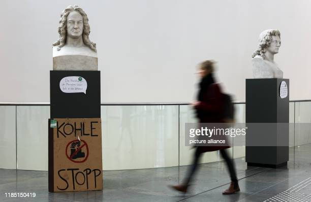 "November 2019, Saxony, Leipzig: A cardboard sign ""Kohle Stopp"" stands at the base of the bust of Gottfried Wilhelm Leibniz during the Climate Action..."